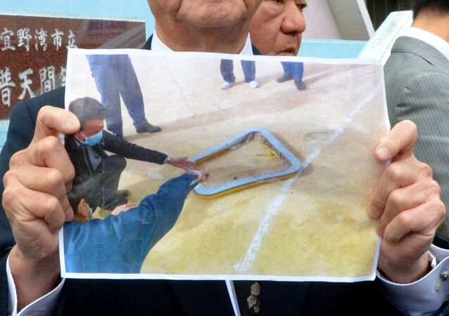 Okinawa Governor Takeshi Onaga shows a picture of a window that fell from a U.S. helicopter onto a school sports field in front of the Futenma Daini Elementary School in Ginowan, Okinawa prefecture, Japan