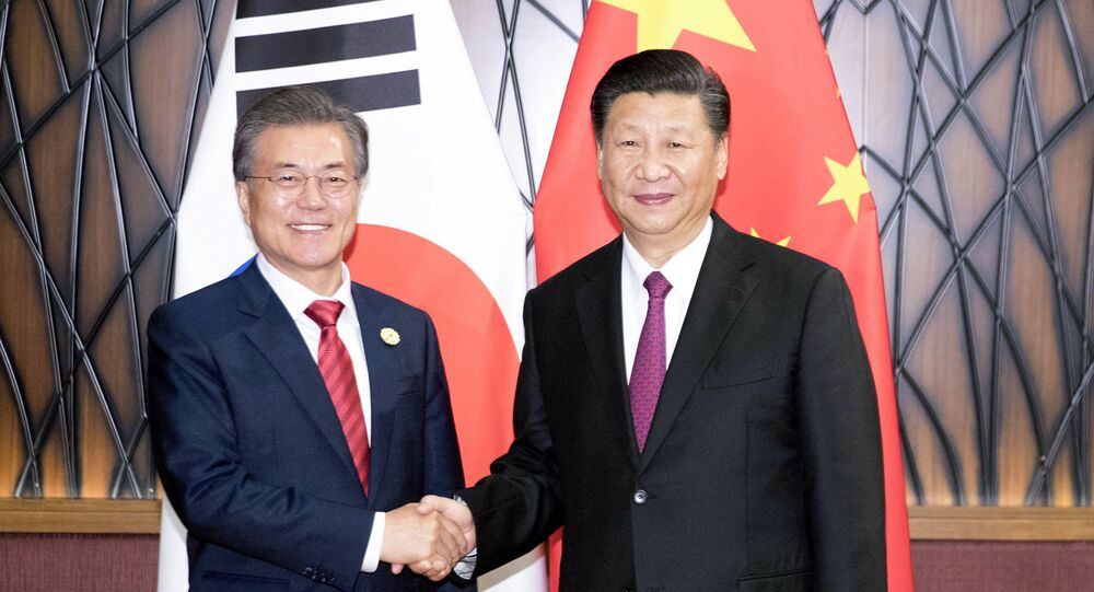 In this Nov. 11, 2017, photo released by China's Xinhua News Agency, South Korean President Moon Jae-in, left, and Chinese President Xi Jinping shake hands as they pose for a photo during a meeting on the sidelines of the Asia-Pacific Economic Cooperation (APEC) Forum in Danang, Vietnam.