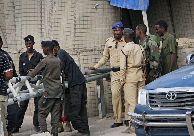 Somali police guard the road leading to the scene of a suicide bomb attack on a police academy in the capital Mogadishu, Somalia Thursday, Dec. 14, 2017