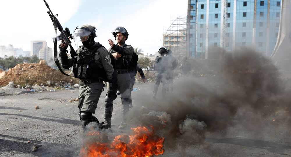 Israeli police officers walk in front of a burned barricade during a protest against U.S. President Donald Trump's decision to recognize Jerusalem as the capital of Israel, near the Jewish settlement of Beit El, near the West Bank city of Ramallah December 11, 2017