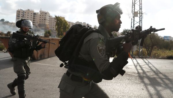 Israeli border policemen run towards Palestinian protesters during a protest against U.S. President Donald Trump's decision to recognize Jerusalem as the capital of Israel, near the Jewish settlement of Beit El, near the West Bank city of Ramallah December 14, 2017 - Sputnik International