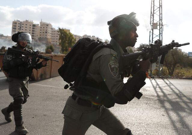 Israeli border policemen run towards Palestinian protesters during a protest against U.S. President Donald Trump's decision to recognize Jerusalem as the capital of Israel, near the Jewish settlement of Beit El, near the West Bank city of Ramallah December 14, 2017