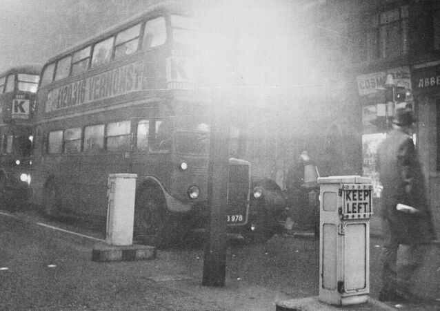 Two of London's double decker buses move slowly through fog shrouded streets, Dec. 5, 1962, as thick smog gripped the city for the second day