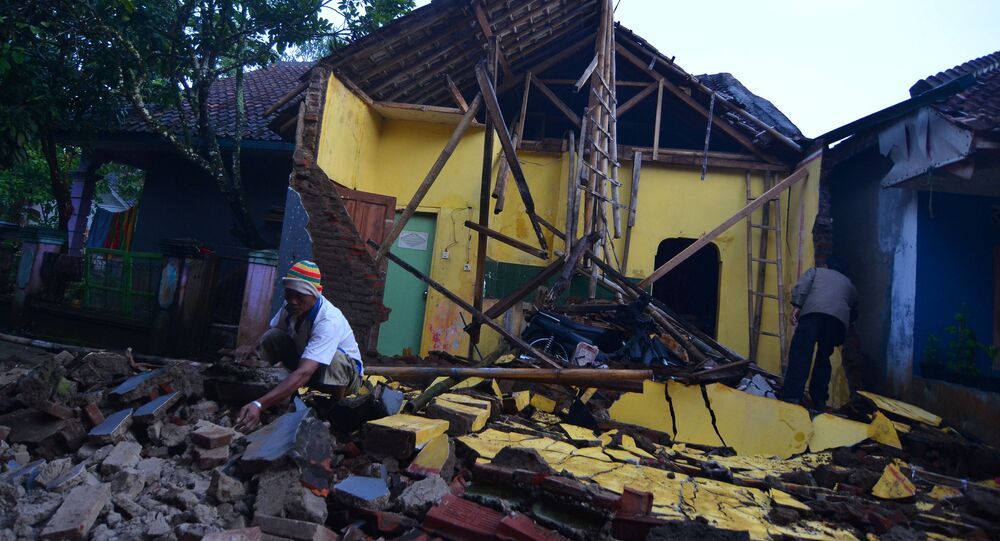 A man cleans up the wreckage of a house damaged by an earthquake in Sumelap Village, Tasikmalaya City, West Java, Indonesia December 16, 2017 in this photo taken by Antara Foto