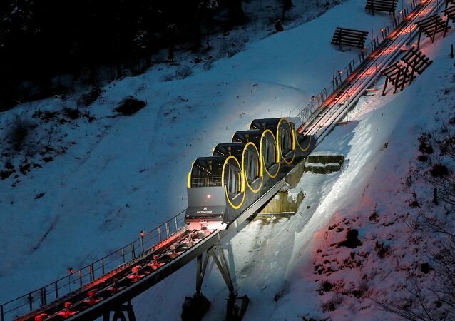 The barrel-shaped carriages of a new funicular line are seen on the illuminated track before the opening ceremony near the Alpine resort of Stoos, Switzerland December 15, 2017