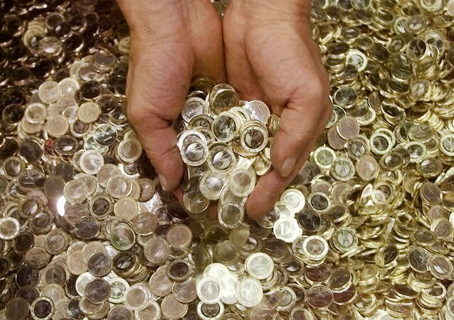 An employee of the national German mint Staatliche Muenze in Berlin holds some Euro coins on Wednesday, Aug. 29, 2001