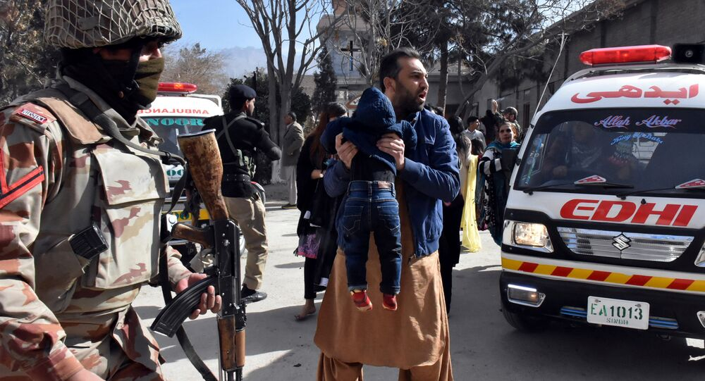 A man carries a boy as he shouts for an ambulance after gunmen attacked the Bethel Memorial Methodist Church in Quetta, Pakistan December 17, 2017