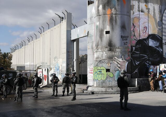 Israeli forces stand near the controversial separation barrier bearing graffiti depecting US President Donald Trump during clashes with Palestinian protestors near an Israeli checkpoint in the West Bank city of Bethlehem on December 7, 2017