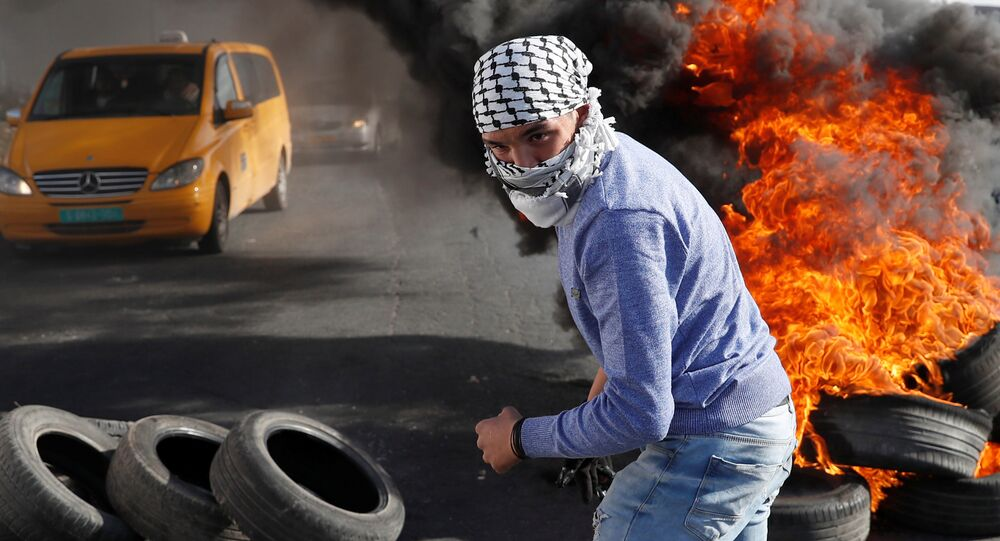 A Palestinian protester walks in front of a burned barricade during a protest against U.S. President Donald Trump's decision to recognize Jerusalem as the capital of Israel, near the Jewish settlement of Beit El, near the West Bank city of Ramallah December 14, 2017