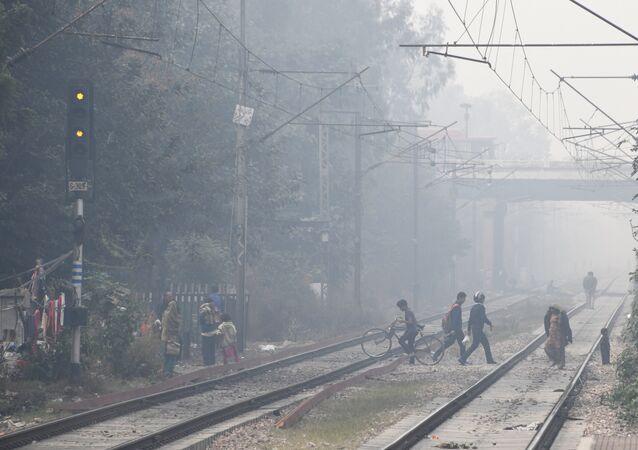 Indian residents walk amid heavy smog near the Lodhi railway station in New Delhi