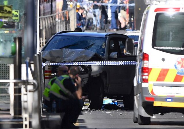 Police sit in front of a crashed vehicle after a driver was arrested after ploughing into pedestrians at a crowded intersection near the Flinders Street train station in central Melbourne, Australia December 21, 2017