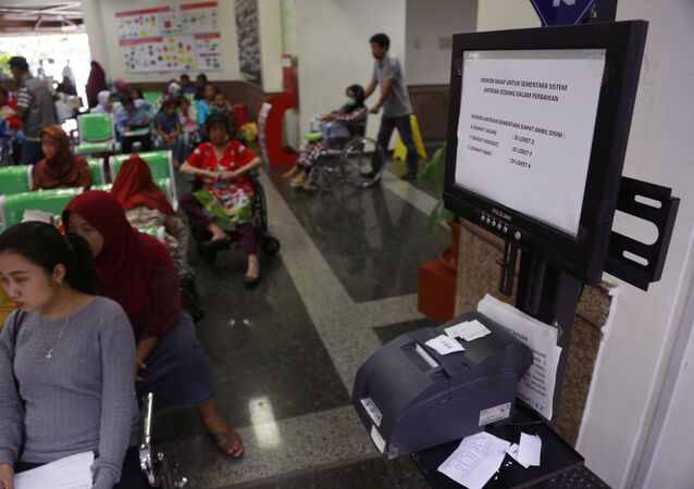 Patients wait near a queue number dispenser affected by WannaCry attack at Dharmais Cancer Hospital in Jakarta, Indonesia, Monday, May 15, 2017