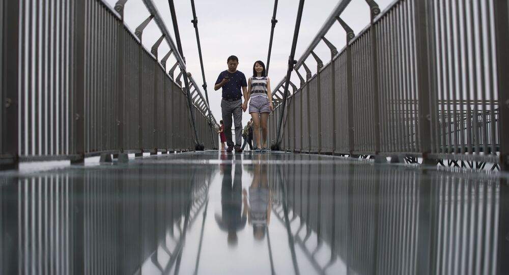 (File) In this photo taken on June 1, 2017, a couple walks on a glass-bottomed skywalk, certified as the world's longest, at the Ordovician park in Wansheng