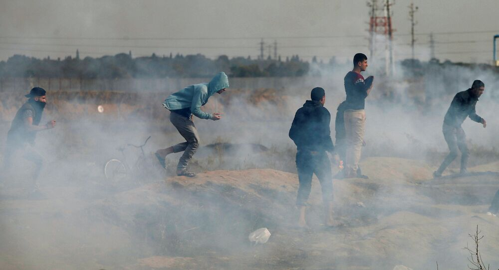 Palestinian demonstrators react to tear gas fired by Israeli troops during clashes at a protest as Palestinians call for a Day of Rage in response to U.S. President Donald Trump's recognition of Jerusalem as Israel's capital, near the border with Israel in the east of Gaza City, December 22, 2017