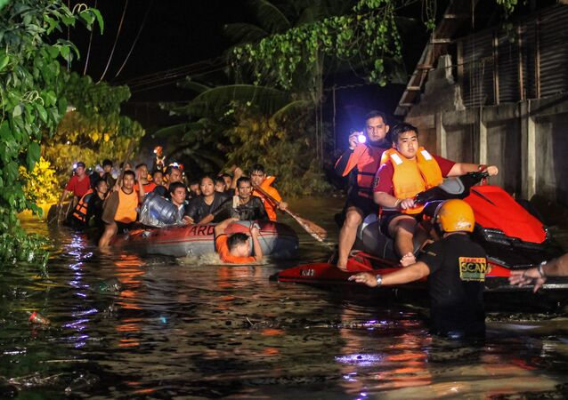 Rescue workers evacuate flood-affected residents in Davao on the southern Philippine island of Mindanao early on December 23, 2017, after Tropical Storm Tembin dumped torrential rains across the island. The death toll from the tropical storm that struck the southern Philippines has risen to 30 with five others missing, officials said on December 23