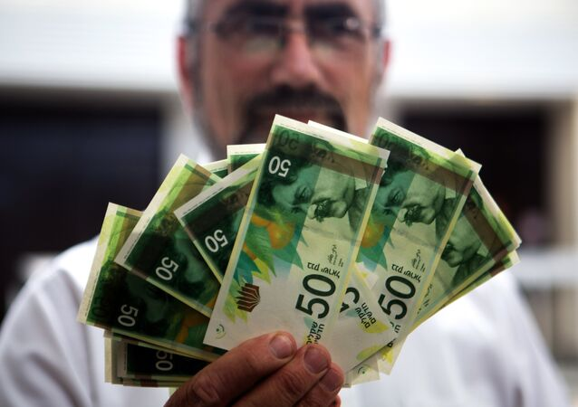 An employee of Bank of Israel holds new 50 Shekels' bills during a press conference at the bank's headquarters in Jerusalem on September 10 2014