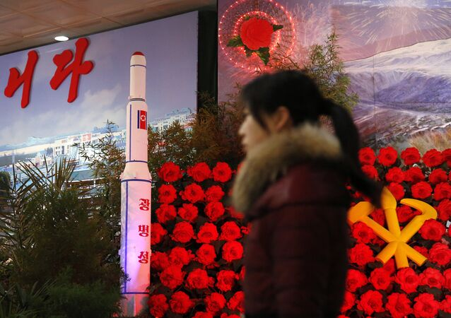 In this Feb. 15, 2016 file photo, a visitor at a flower festival walks past a model of North Korea's newest satellite Kwangmyongsong 4 on display