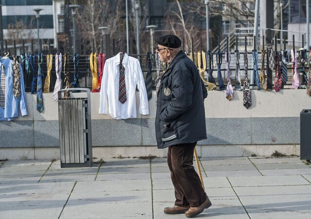 A man passes by hundreds of collected ties and shirts hanging on the fence of the government building on Tuesday, Dec. 26, 2017, in Kosovo capital Pristina