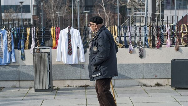 A man passes by hundreds of collected ties and shirts hanging on the fence of the government building on Tuesday, Dec. 26, 2017, in Kosovo capital Pristina - Sputnik International