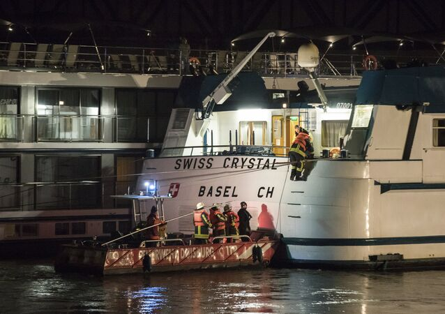 In this Dec. 26, 2017 photo rescuers arrive at a tourist ship in Duisburg, Germany. A tourist ship has struck a highway bridge on the Rhine river in western Germany
