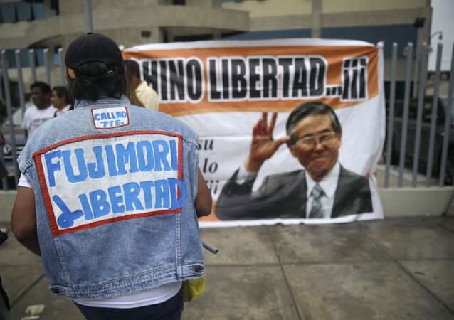 A supporter of former President Alberto Fujimori wears a jacket that says in Spanish Free Fujimori outside the clinic where the jailed leader was admitted the previous day after suffering a drop in blood pressure in Lima, Peru, Sunday, Dec. 24, 2017. The former strongman, who governed from 1990 to 2000, is a polarizing figure in Peru. Some Peruvians laud him for defeating the Maoist Shining Path guerrillas, while others loathe him for human rights violations carried out under his government. (AP Photo/Martin Mejia)