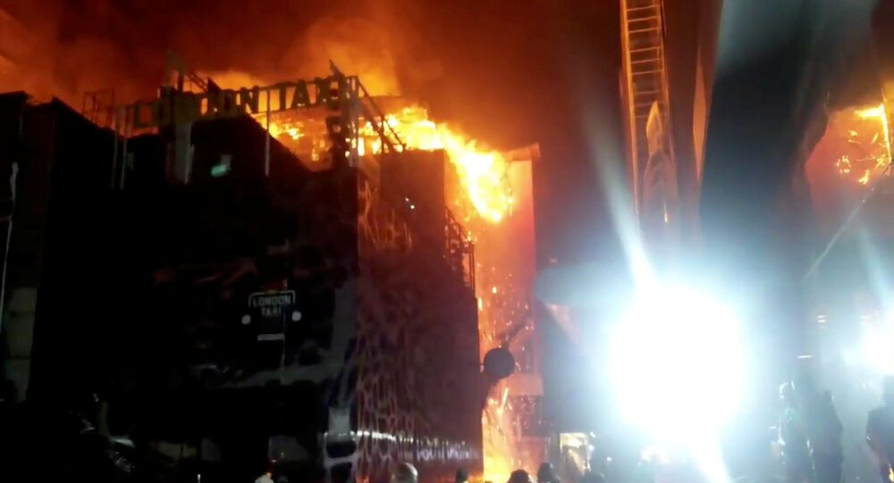 Debris falls from a building on fire in Mumbai, India, in this still image taken from a social media video, on December 29, 2017