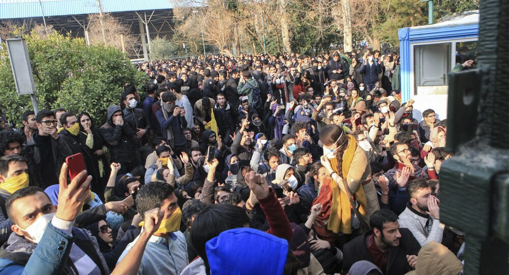 In this photo taken by an individual not employed by the Associated Press and obtained by the AP outside Iran, university students attend a protest inside Tehran University while anti-riot Iranian police prevent them to join other protestors, in Tehran, Iran, Saturday, Dec. 30, 2017