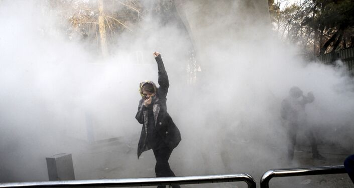 FILE - In this Saturday, Dec. 30, 2017 file photo taken by an individual not employed by the Associated Press and obtained by the AP outside Iran, a university student attends a protest inside Tehran University while a smoke grenade is thrown by anti-riot Iranian police, in Tehran, Iran