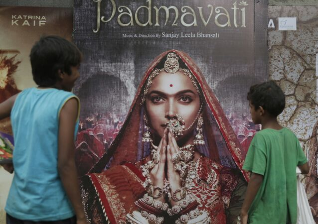 Boys look at a poster of Bollywood film 'Padmavati' in Mumbai, India, Tuesday, Nov. 21, 2017.