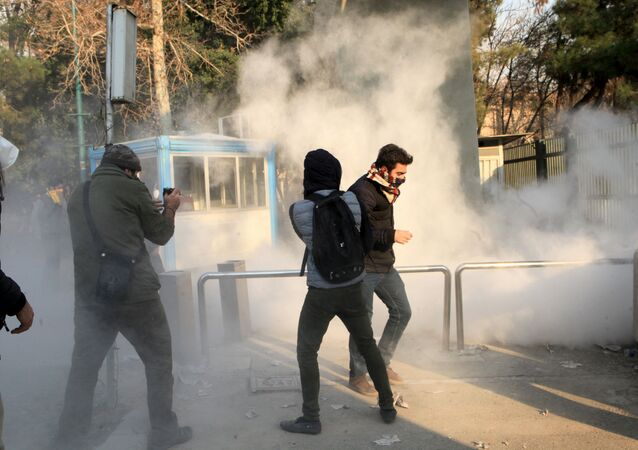 Iranian students run for cover from tear gas at the University of Tehran during a demonstration driven by anger over economic problems, in the capital Tehran on December 30, 2017
