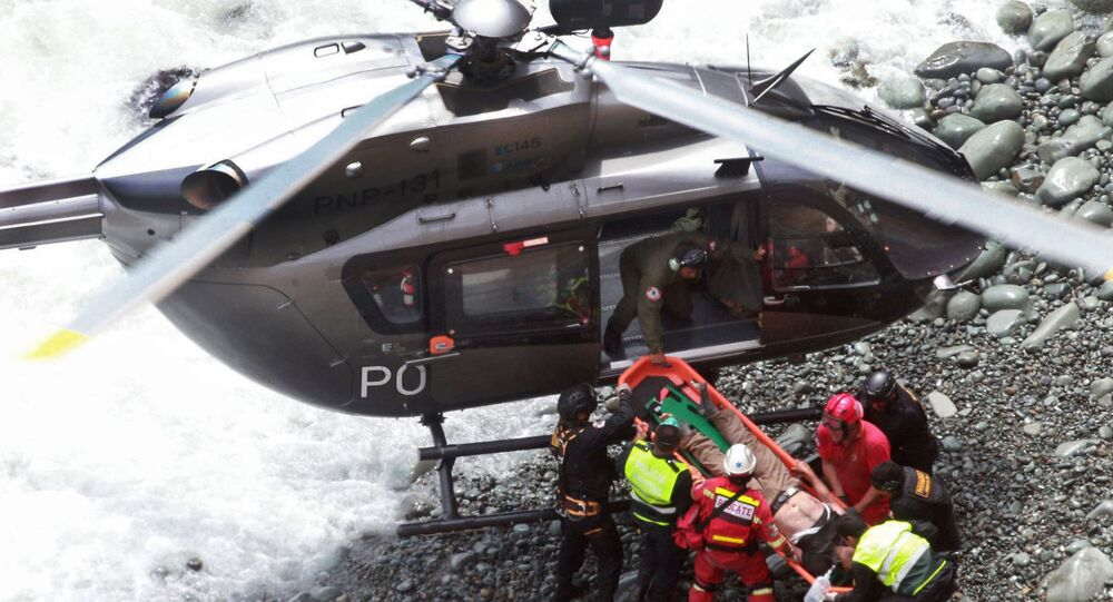 In this photo provided by the government news agency Andina, rescue workers load an injured man on a stretcher after he was retrieved from a bus that fell off a cliff after it was hit by a tractor-trailer rig, in Pasamayo, Peru, Tuesday, Jan. 2, 2018.