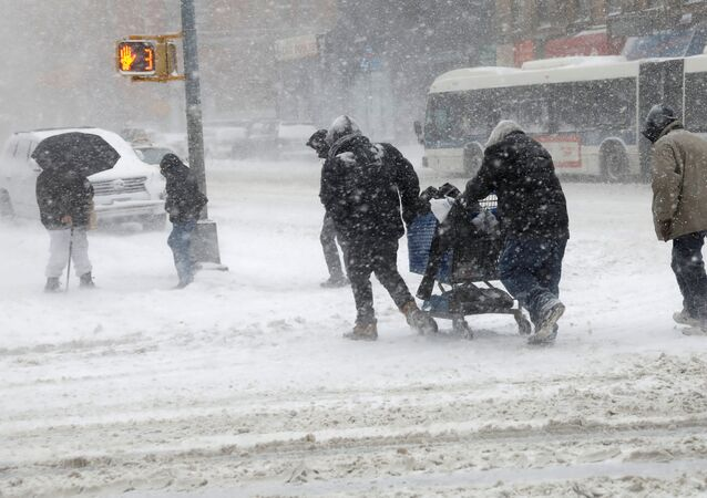 People struggle against wind and snow as they cross 125th street in upper Manhattan during a snowstorm in New York City, New York, U.S., January 4, 2018