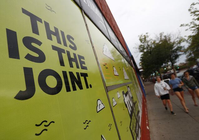 In this Sunday, Aug. 20, 2017, photo, a sign is affixed to the window of an information cafe named Mutiny as pedestrians pass by in south Denver. Shop owner Jim Norris is hoping to license his storefront as one of the nation's first legal marijuana clubs.