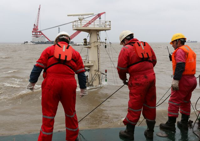 (File) Rescue workers work on a rescue ship at the site where a cargo vessel sank following a collision with another vessel