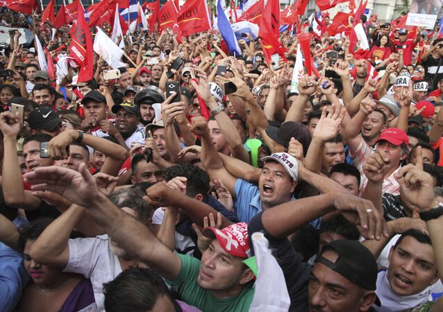 Opposition supporters cheer during a rally where Salvador Nasralla reaffirmed his claim on the presidency of Honduras, in the central park of San Pedro Sula, Honduras, Saturday, Jan. 6, 2018