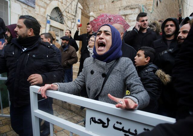 A demonstrator reacts during a protest against the visit of Greek Orthodox Patriarch of Jerusalem Theophilos III, in the West Bank city of Bethlehem January 6, 2018