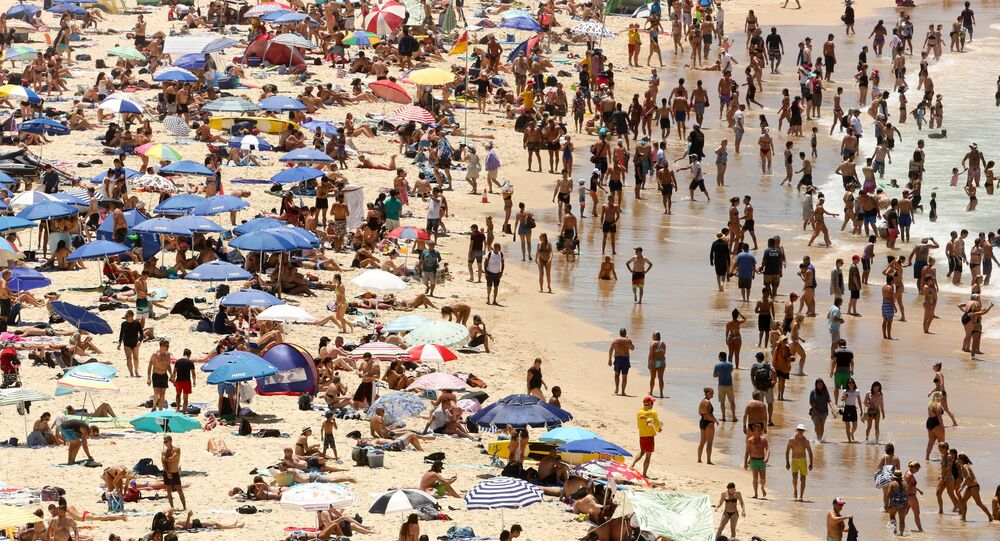 Beachgoers sit and walk in the water at Sydney's Bondi Beach on a hot summer day in Australia, January 7, 2018