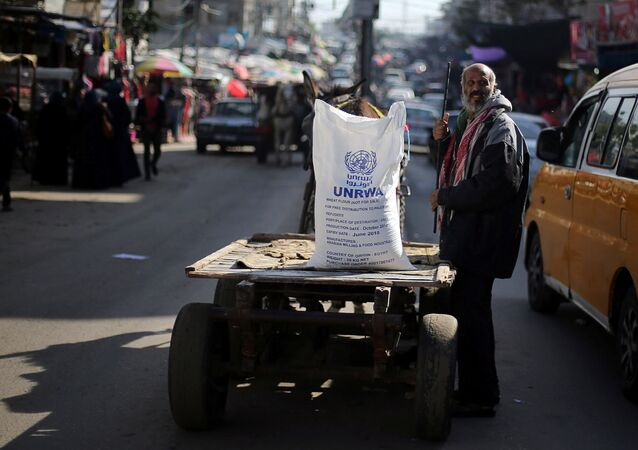 A Palestinian man stands next to a cart carrying a flour sack distributed by the United Nations Relief and Works Agency (UNRWA) in Khan Younis refugee camp in the southern Gaza Strip January 3, 2018