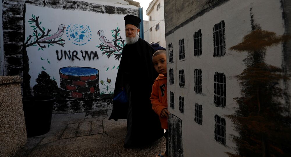 A Palestinian man walks past a logo of United Nations Relief and Works Agency (UNRWA) in Jalazone refugee camp, near the West Bank city of Ramallah January 3, 2018