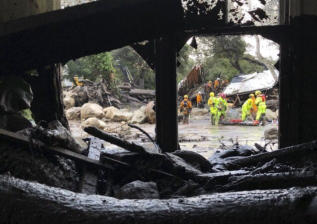 In this photo provided by Santa Barbara County Fire Department, firefighters respond to mud and debris flow due to heavy rain in Montecito.
