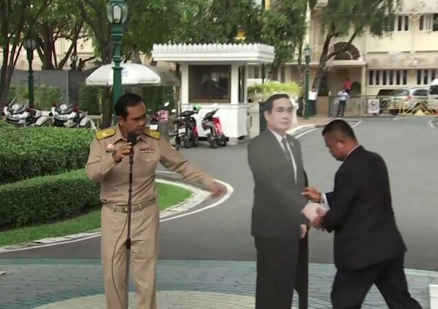 In this image from video, Thailand's Prime Minister Prayuth Chan-ocha, left, directs the scene as a life-sized cardboard cut-out figure of himself is carried into view by an aid, in Bangkok, Thailand, Monday Jan. 8, 2018.