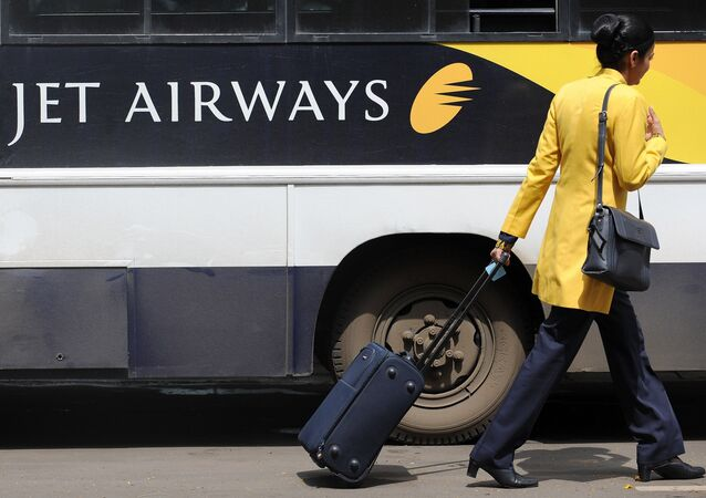 A Jet Airways flight attendant walks past a company coach at the city airport in Mumbai (File)