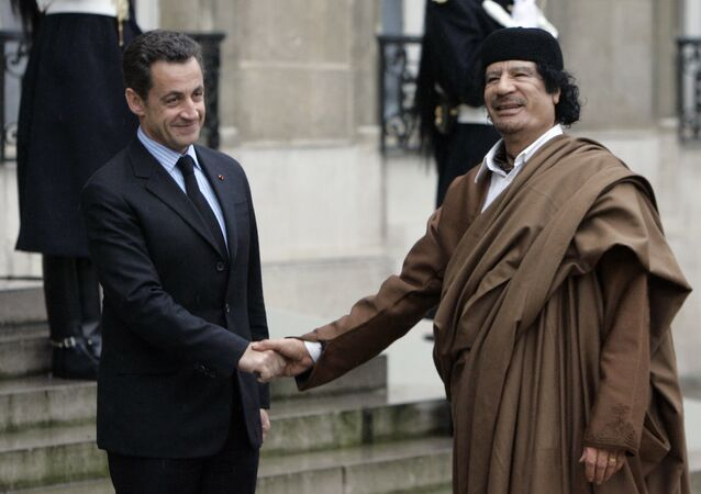 French President Nicolas Sarkozy, left, greets Libyan leader Col. Moammar Gadhafi upon his arrival at the Elysee Palace, in Paris. (File)