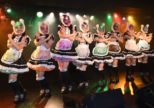 Female idol group Kasotsuka Shojo (Virtual Currency Girls), produced by Japanese idol agency Cinderella Academy, pose on stage in Tokyo