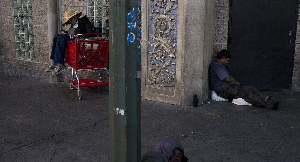 Three homeless people take a nap on a sidewalk in the Skid Row area of downtown Los Angeles