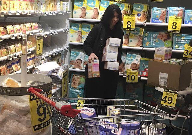 Pharmacist Deborah Cohen removes boxes of baby mils in Paris, Thursday, Dec. 21, 2017