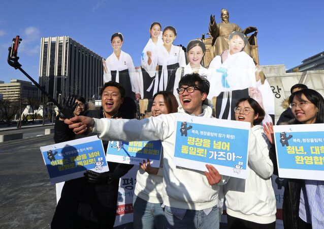 College students take a selfie with cutouts of North Korean cheerleaders during a rally to welcome the outcome of a meeting between South and North Korea, in Seoul, South Korea, Wednesday, Jan. 10, 2018