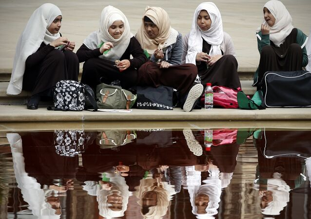 Young girls eat their lunch beside a pond at the V&A Museum in London on April 2, 2014