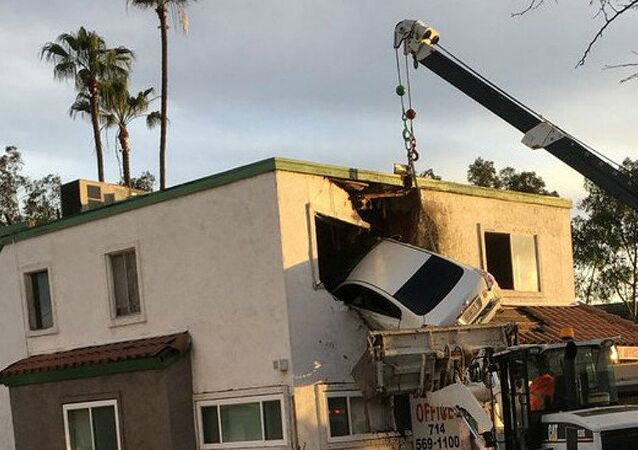 Rescue workers remove a car that crashed into a building after speeding into a median and going airborne, according to local media, in Santa Ana, California, U.S., January 14, 2018, in this picture obtained from social media