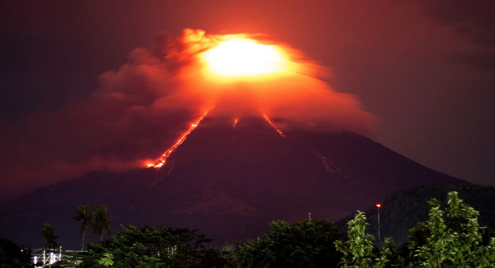 Lava cascades down the slopes of Mayon volcano as seen from Legazpi city, Albay province, around 340 kilometers (210 miles) southeast of Manila, Philippines, Monday, Jan. 15, 2018. More than 9,000 people have evacuated the area around the Philippines' most active volcano as lava flowed down its crater Monday in a gentle eruption that scientists warned could turn explosive.